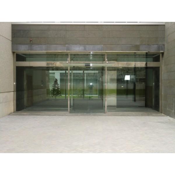 Puerta corredera de cristal con escaparate de acero y marquesina